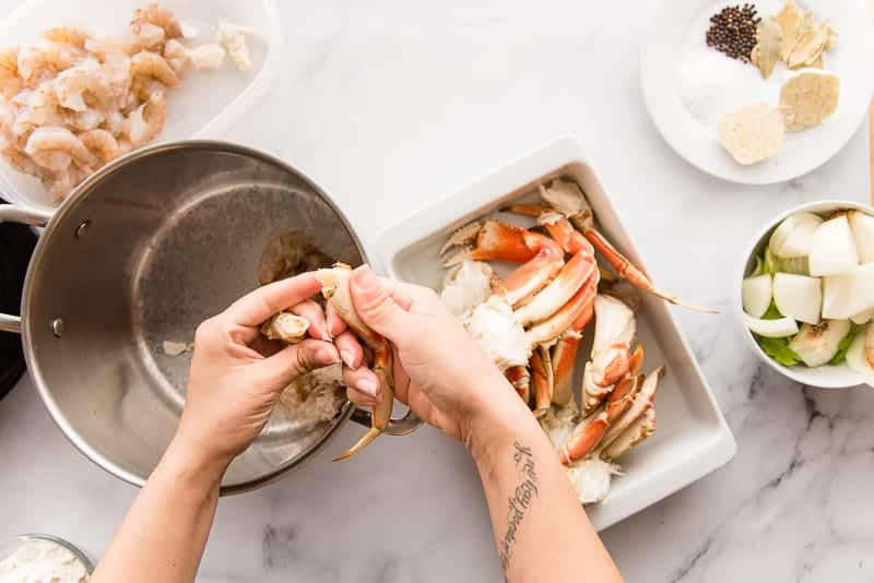 Hands break crab legs apart to extract its meat