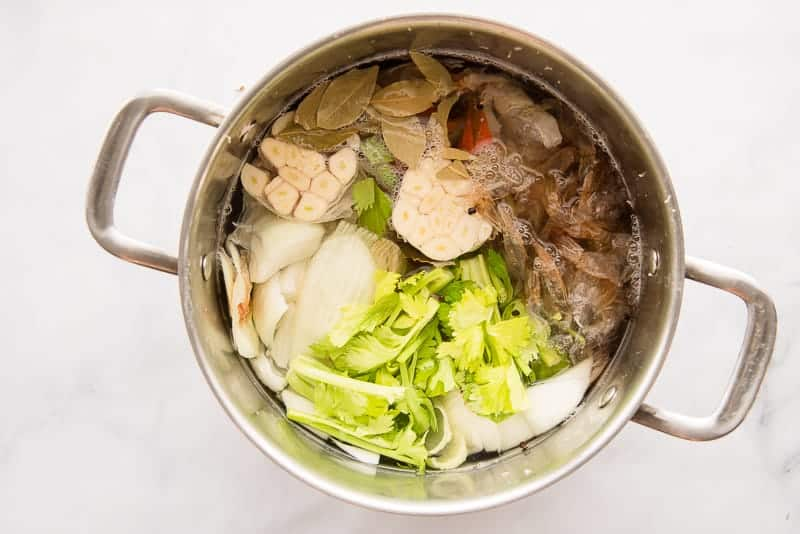 Stock ingredients are combined in a pot and covered with water.