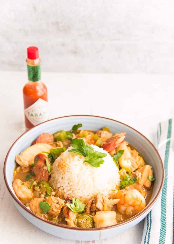 Lead image: portrait of a blue bowl of gumbo with rice in the center garnished with parsley. A bottle of tabasco in the background to the left.