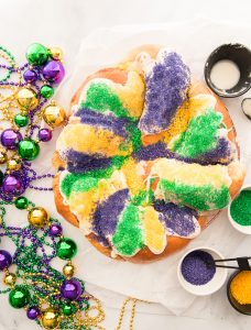 Overhead image of a sugared King Cake surrounded by beads and sanding sugar.
