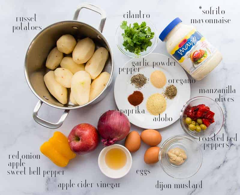 Ingredients for Puerto Rican Potato Salad: russet potatoes in a silver pot, cilantro, mayonnaise, spices, olives, red peppers, dijon mustard, eggs, apple cider vinegar, pepper, apple onion.