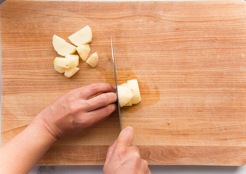 Hands cut russet potatoes with a knife on a wooden cutting board.