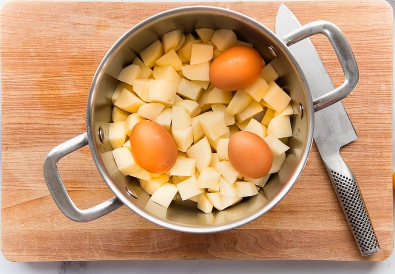 Chopped potatoes and brown eggs in a silver pot on a wooden cutting board