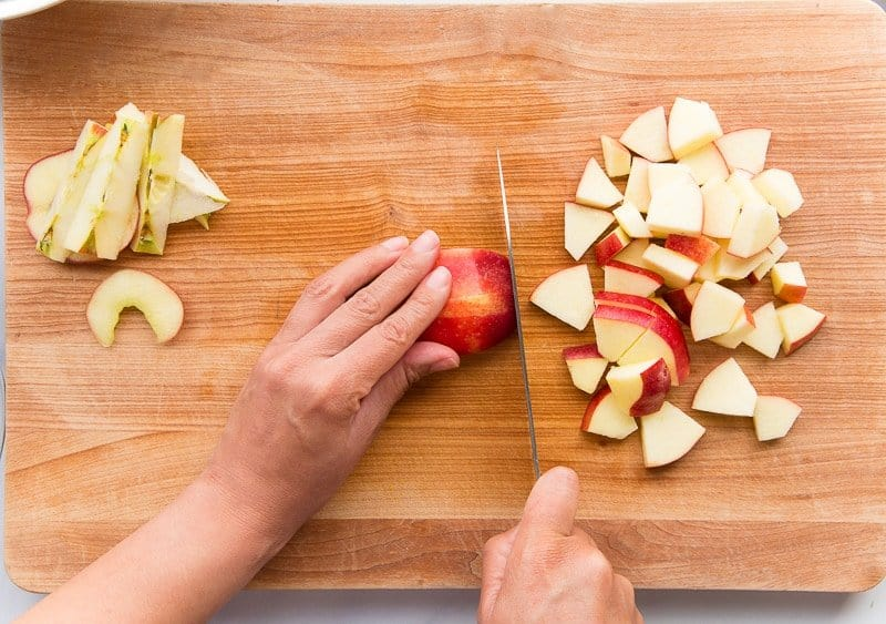 Hands cut red apples on a wooden cutting board