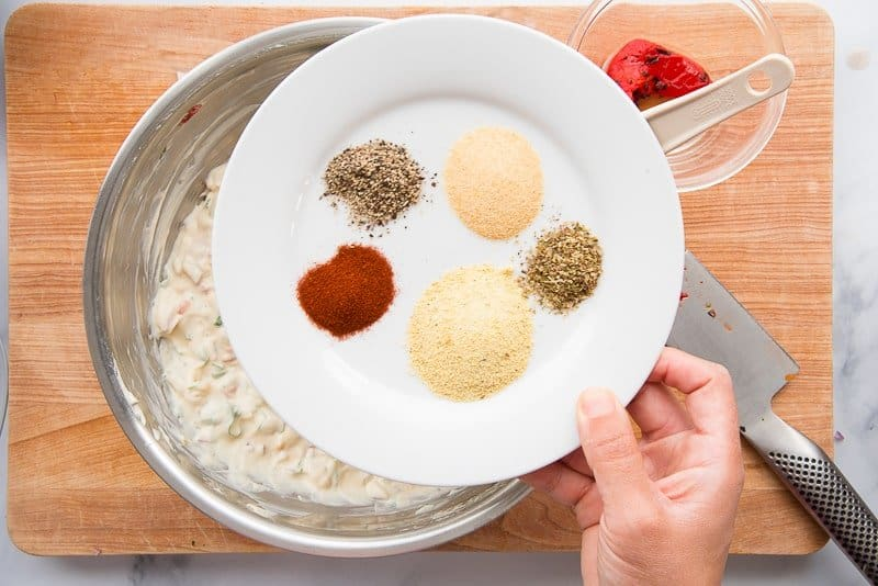 Spices on a white plate above a silver mixing bowl