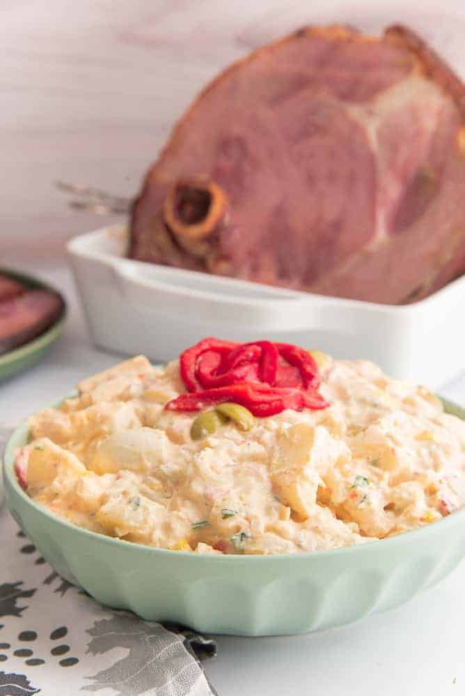A green serving bowl of Puerto Rican Potato Salad. Red pepper garnish on top. Top left of image a white roasting pan with a ham.