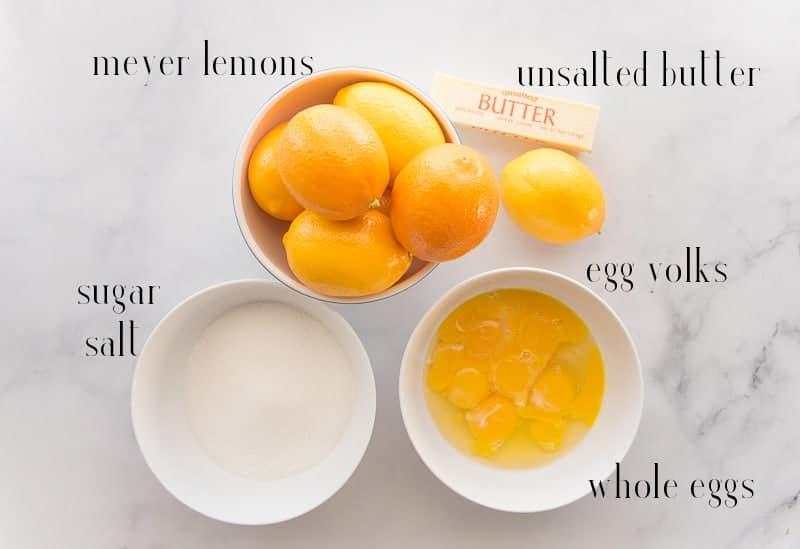 Ingredients to make Meyer Lemon Curd: meyer lemons, butter, eggs, sugar, and slat on a blue background