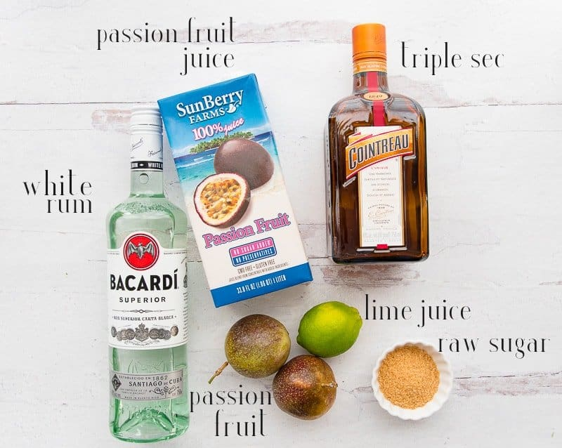 Ingredients for Classic Passion Fruit Daiquiri shown on a white surface: passion fruit juice, triple sec, lime juice, raw sugar, passion fruit, and white rum.
