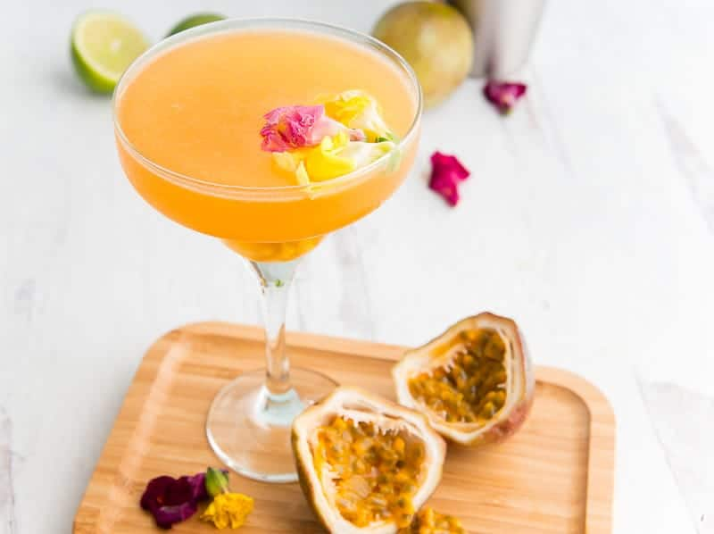 Orange Classic Passion Fruit Daiquiri cocktail in a coupe glass garnished with yellow and pink edible flowers