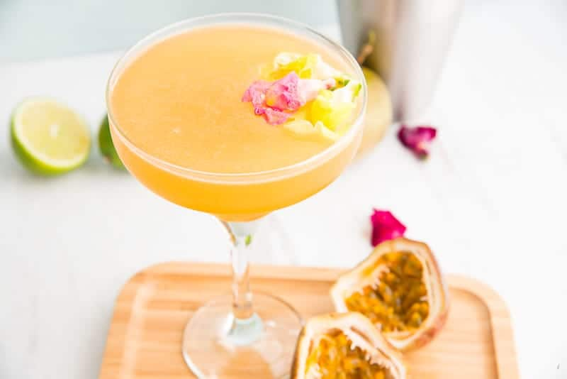 3/4 view of a coupe glass filled with orange cocktail garnished with pink and yellow edible flower buds