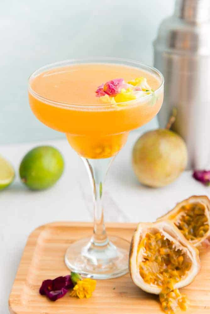 Lead image of a Classic Passion Fruit Daiquiri on a wooden plate next to a passion fruit that's halved.