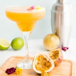 Preview image of a clear coupe glass of Classic Passion Fruit Daiquiri on a wooden plate with a half of a passion fruit split open.