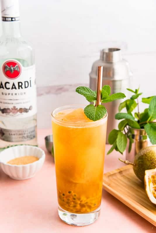 Passion Fruit Mojito in a highball glass with a mint sprig and a copper straw in front of a bottle of Bacardí rum