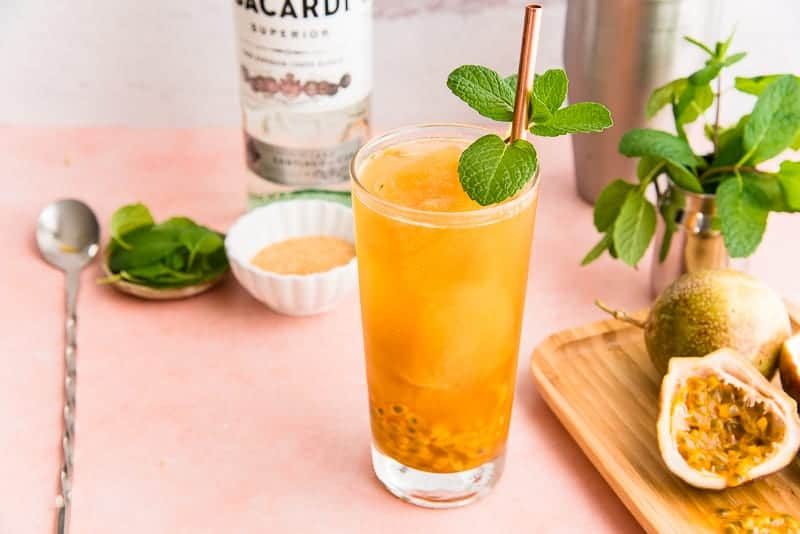 Horizontal image of a Passion Fruit Mojito in a highball glass next to a silver cocktail stirrer.
