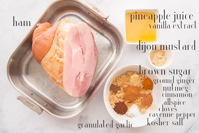 Ingredients to make Ham with Spiced Brown Sugar Pineapple Glaze on a white surface: ham pineapple juice, vanilla extract, mustard, and spices
