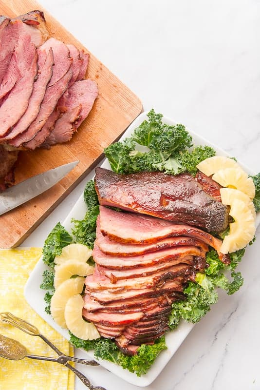 Overhead image of sliced Ham with Spiced Brown Sugar Pineapple Glaze on a white platter and a bed of greens