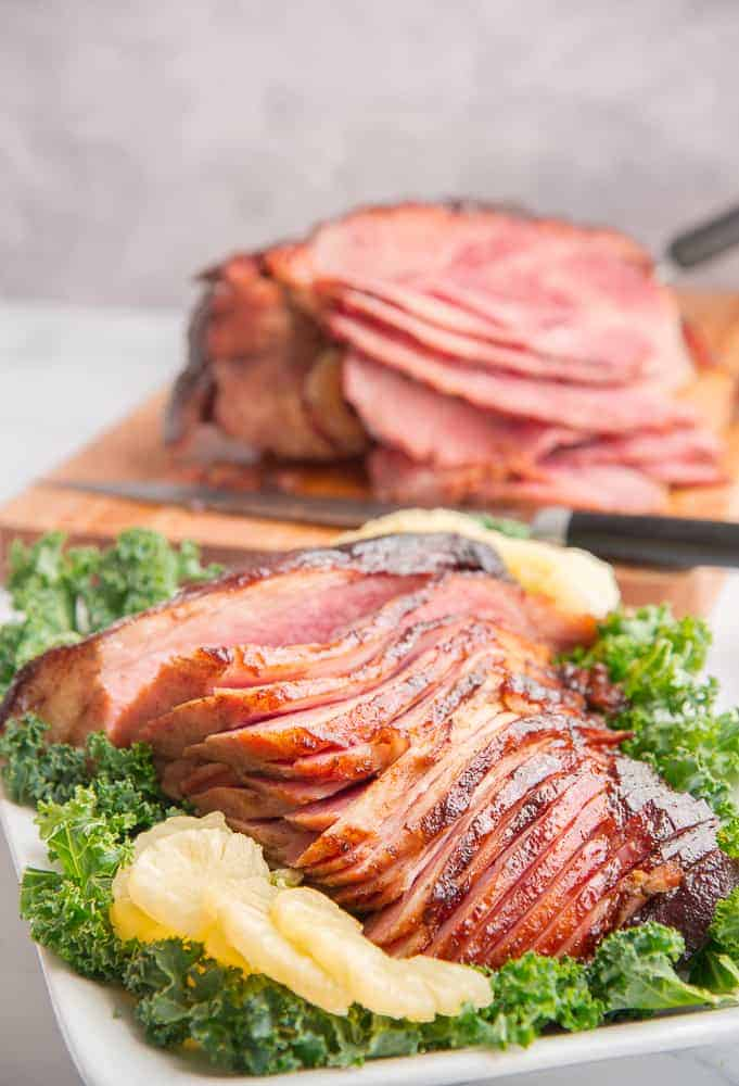Lead image of Ham with Spiced Brown Sugar Pineapple Glaze on a bed of kale in front of a cutting board with the rest of the ham.