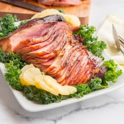 Preview image of Ham with Spiced Brown Sugar Pineapple Glaze on a bed of kale surrounded by sliced pineapples