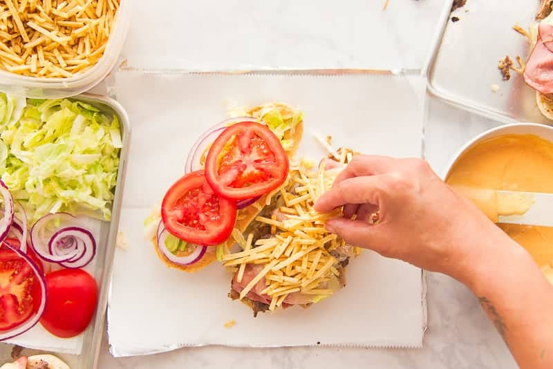 A hand adds shoestring potatoes to a half of the sandwich.