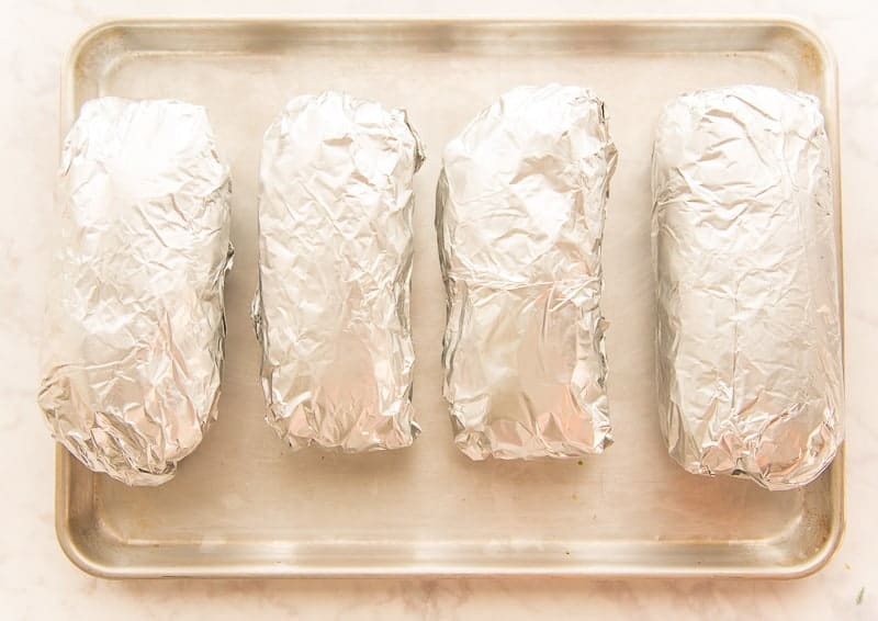Tripletas wrapped in foil on a sheetpan before being toasted in the oven