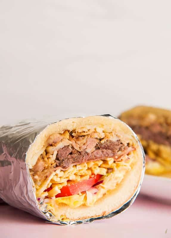 Close-up, horizontal image of half of a Tripleta sandwich wrapped in foil on a pink surface