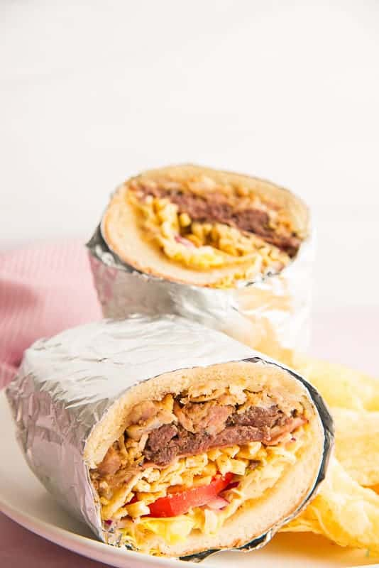 Long image of a foil-wrapped tripleta sandwich cut in half to show the interior on a white plate