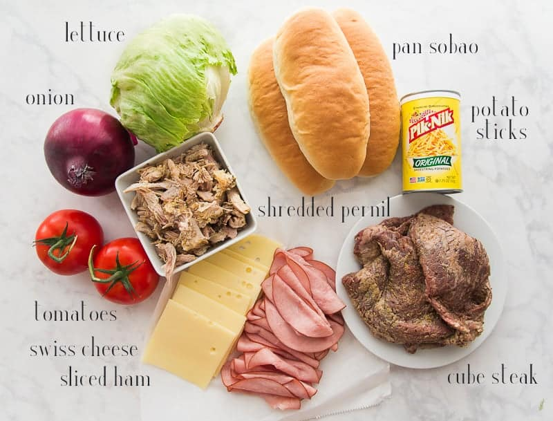 The ingredients needed to make Tripletas: lettuce, pan sobao, potato sticks, cube steak, ham, swiss cheese, shredded pernil, tomatoes, and onion