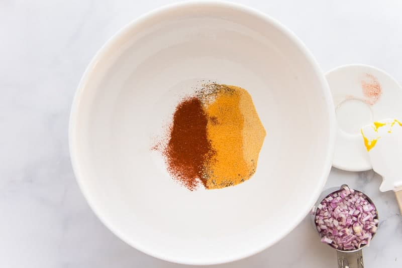 Spices added to a white ceramic bowl