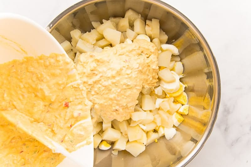 The sweet pickle relish dressing is poured over the cooked potato and eggs in a silver mixing bowl.