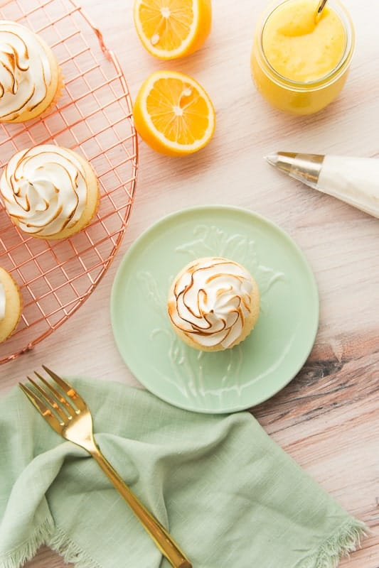 Portrait of a Lemon Meringue Cupcake on a small green plate surrounded by a piping bag, glass of lemon curd, and the rest of the cupcakes.