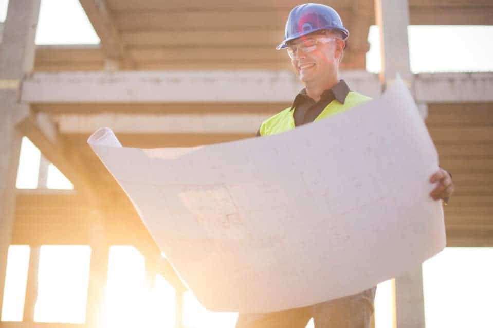 Builder holding plans in hand for a custom build home