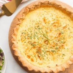 Overhead horizontal image of a baked quiche lorraine on a wooden board