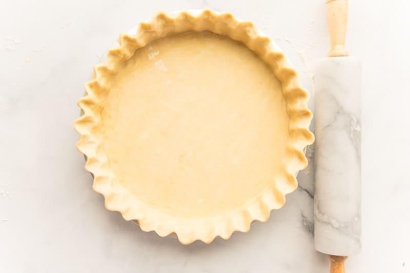 Pie dough shell next to a marble rolling pin