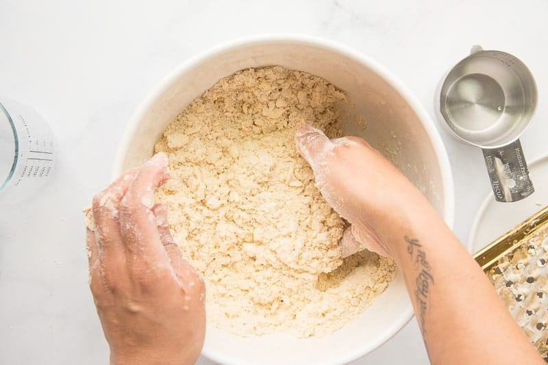A hand tosses ice water into the pie dough mixture in a ceramic bowl