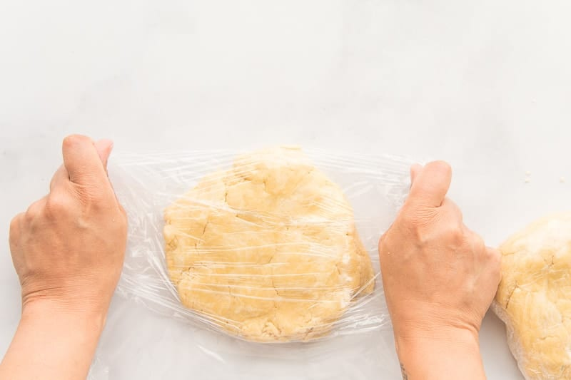 Flaky pie dough is wrapped in plastic film