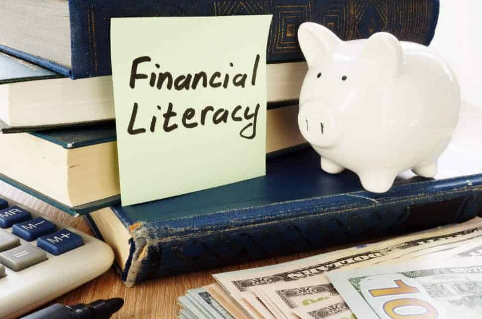 Sticky note with Financial Literacy written on it next to a piggy bank