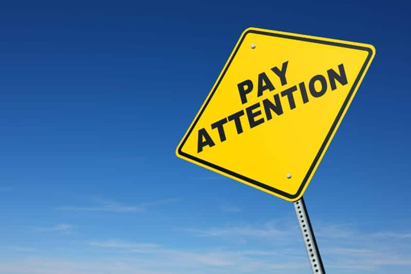 Yellow Pay Attention sign against blue background