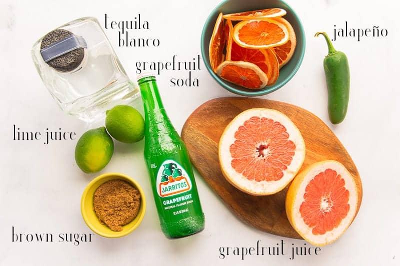Ingredients to make a Spicy Paloma Cocktail: tequila blanco, grapefruit soda, jalapeño, grapefruit juice, brown sugar, and lime juice.