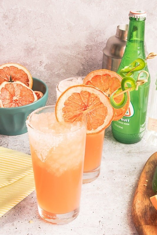 Spicy Paloma Cocktails in front of a green bottle and a teal bowl filled with dried grapefruit slices