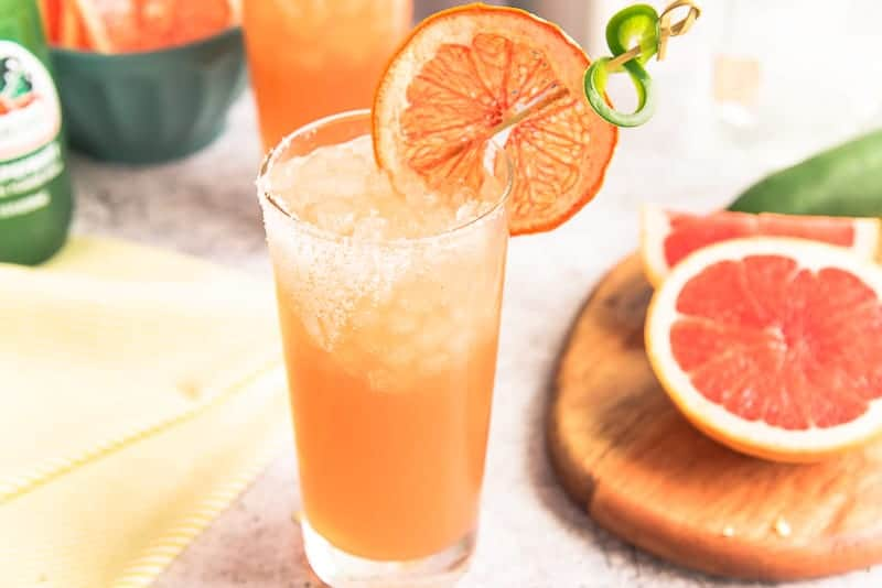 A highball glass with orange Spicy Paloma Cocktail next to a wooden cutting board with a grapefruit half.