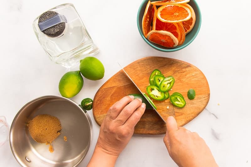 Hands use a knife to slice a jalapeño pepper on a wooden cutting board