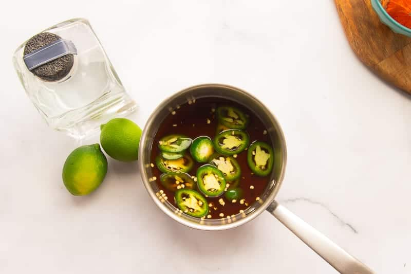 Brown sugar, water, and jalapeños in a pot to make simple syrup
