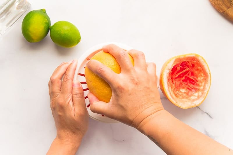 Hands squeeze the juice from a grapefruit
