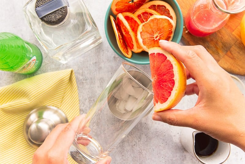 A grapefruit rubbing on the rim of a highball glass to wet it for a salt rim.