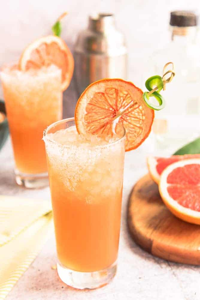 Portrait of a highball of Spicy Paloma cocktail in a highball glass with a grapefruit and jalapeño garnish.