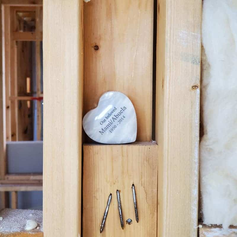 An urn placed inside the framing of a new home.