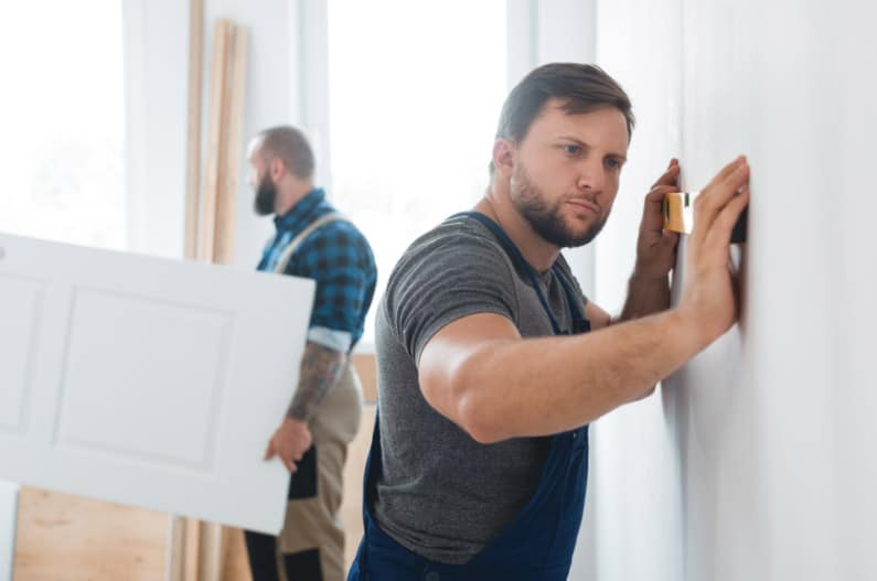 Man leveling a wall. Punch lists and closing blog post.