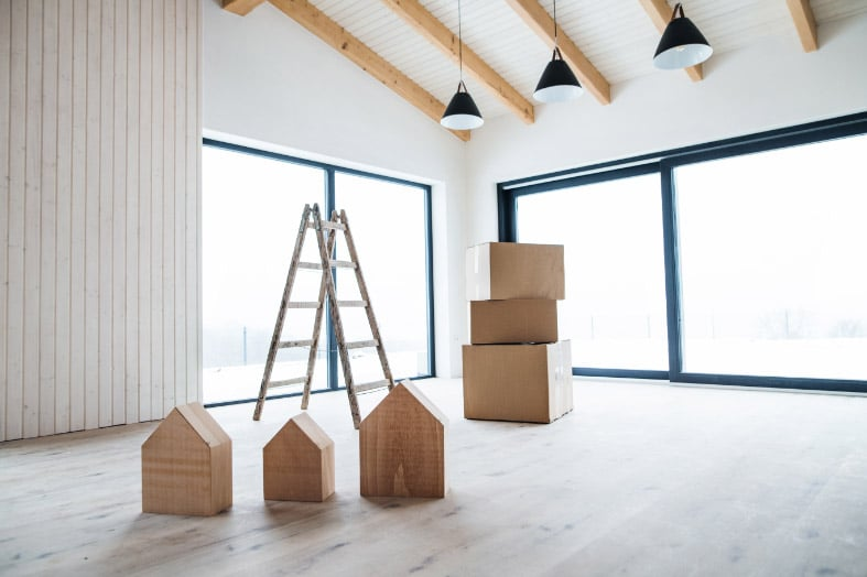 Three wooden houses in an empty house in front of stacked moving boxes and an a-frame ladder