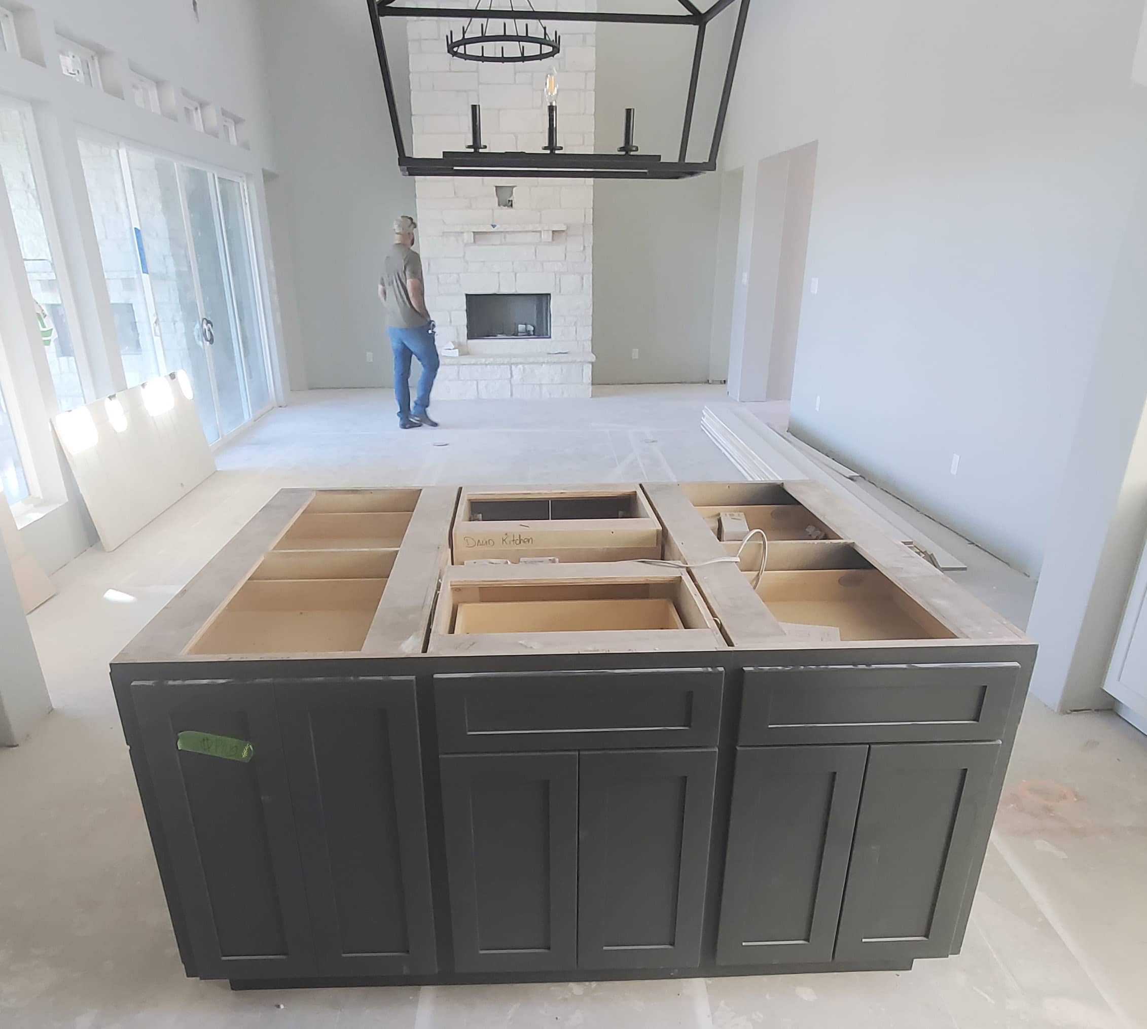 Unfinished kitchen cabinets in foreground, man is green shirt and jeans in background