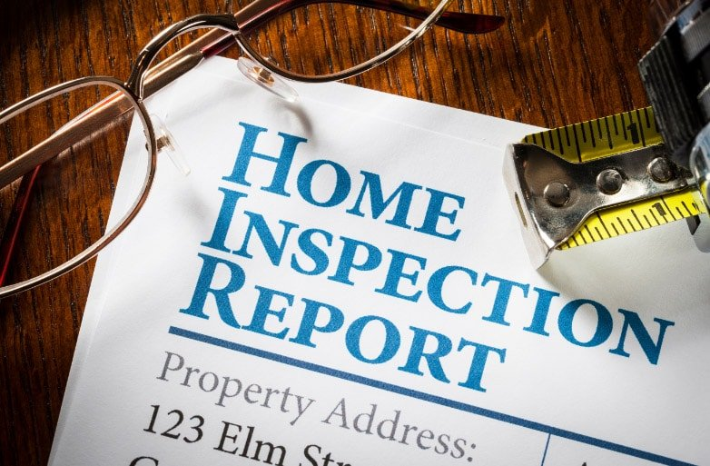White piece of paper with blue text that reads Home Inspection Report part of Punch lists and closing